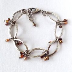 What a beautiful fine silver link bracelet with lustrous fresh water pearl drops. The fresh water pearls vary in color from taupe, copper and brown. For a bit of sparkle I've added dark brown Swarovsk