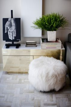 "thebowerbirds: ""Source: Vogue Living Loving all the textures and finishes going on here. Tibetan lambs wool ottoman, hide rug and brass side table topped with some some fresh greenery makes for a..."
