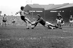 Alex Stepney of Manchester United saves at the feet of Jim McCalliog of Wolves.