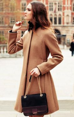 camel wool tunic coat with flat front, covered buttons and cinched back. natural/mussed ombre hair, thinned but not layered in medium length. bronzey eye with brown liner, tangerine nails (bright warm tone). black structured crossbody