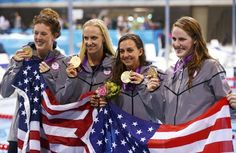 The U.S.'s Schmitt, Vollmer, Soni and Franklin pose with their gold medals and national flag after winning the women's 4x100m medley relay final