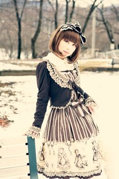 Elegant, classic lolita: Black bow headdress with white lace. Dark gray cardigan with white lace details and bow. Brown and white barred dress with pattern.