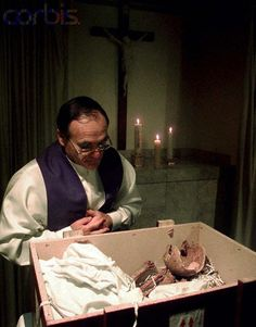 Reverend Domonic Spinosi blesses the remains believed to be those of the Grand Duchess of Russia Anastasia Romanov at a funeral parlor. The remains were blessed before being prepared by a forensic scientist for dispatching to Oxford University for DNA profiling