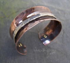 Smooth copper and textured Sterling silver provide for an interesting contrast in this cuff-style bracelet. Tiny brass screw rivets hold the heavy silver strip in place and a deep rich patina enhances the the texture and beauty of the metals.