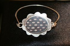Sterling silver flower bracelet with gray resin with cream and red oval dots by artist Jennie Milner! On display and for sale at Outnumbered Gallery in Downtown Littleton, Colorado!