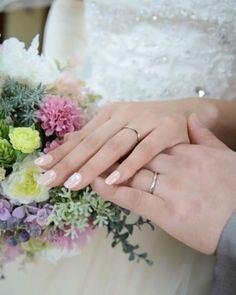 結婚指輪を見せるように手を重ねた