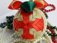 Traditional Christmas ornament is made of gold glitter, red and green satin ribbon placed on a styrofoam ball by technique pineapple . I used cotton lace