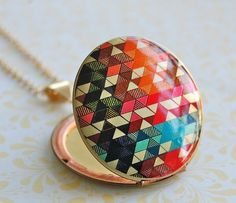 "An authentic vintage locket features the original illustration, ""Color Study"" by artist/designer, Alyson Fox"