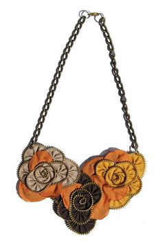 Collar  pegado al cuello hecho con cierres reciclados y retazos de tela, colores en diferentes tonos de amarillos y cafés. Ferzu es una marca creativa que ha estado presente en varios desfiles de moda ya y este collar es de la colección Hanabi Takai, inspirado en las formas de los juegos pirotécnicos. $239