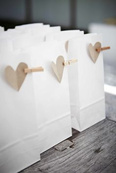 White paper bags, mini pegs and brown card or burlap hearts. Cheap but cute!