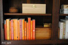 living room. black walnut cupboard shelf. orange books.