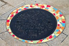 Manhole cover with bicycle design, surrounded by mosaic;  Taipei, Taiwan;   photo by David Yeo T. B., via Flickr