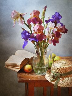 http://pixels.com/products/iris-flowers-and-straw-hat-nikolay-panov-art-print.html floral still life photography with bouquet of blue and pink iris flowers in glass pitcher, yellow apples, old open book and summer straw hat on rustic wooden table in countryside in June