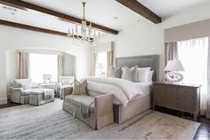 Elegant bedroom features a dove gray velvet bed dressed in white bedding and gray geometric velvet pillows flanked by gray chests doubling as nightstands and white oval lamps tucked under windows covered in gray cornice boxes with matching curtains.