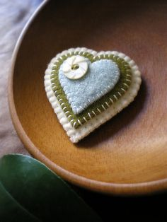 """wool, felt heart (ornament, bowl ornie or wearable pin). This would be cute made from a """"felted wool sweater"""" + cut-out wool heart stitched together with cute, vintage button! Fabric Crafts, Sewing Crafts, Crochet Amigurumi, Penny Rugs, Wool Applique, Felt Christmas, Christmas Ornament, Christmas Decor, Felt Hearts"""