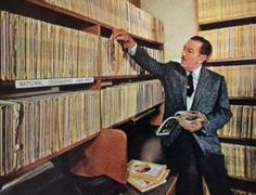 """Walt Disney with his extensive collection of """"National Geographic"""" magazines."""