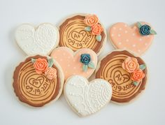 Wedding cookie favours.  Decorated sugar cookies, Peach polka dot, white lace and wood rounds with navy and peach roses.  Initials and date inscribed on wood tree log cookies