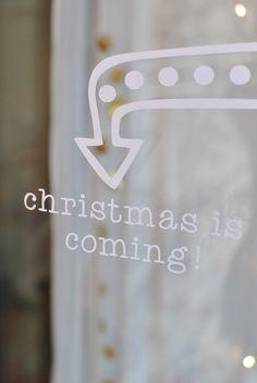 """Sticker représentant une flèche et texte  """"christmas is coming"""", à la manière des décorations lumineuses municipales. Petite étiquette assortie jointe.Blanc mat.Dimensions : 15x 11 cmA coller sur une fenêtre, une cloche en verre, un globe de mariée. On annonce Noël de façon joyeuse!Joli aussi sur un tableau noir.Le sticker est recouvert de papier transfert et livré avec une petite raclette d'aide à la pose. A poser sur une surface lisse. Non rep..."""
