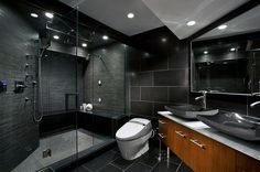 Stylish modern master bathroom ideas with wooden vanity plus white granite top also double grey vessel sink and white toilet as well as glass door shower room plus hidden ceiling lights.