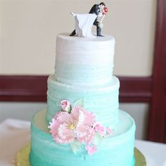 The teal ombre cake had three tiers and was decorated with a bright pink sugar flower.