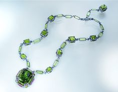 The Chest of Treasures by Wallace Chan with a 132 ct peridot, diamonds and amethyst. The luxuriant and luscious olive green of the peridot is adorned with amethyst. The peridot has strong birefringence, which is also known as double refraction adding allure to the stone.The necklace intertwines peridot slices and diamonds.
