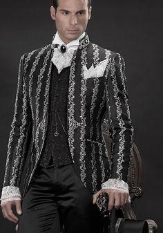 Bräutigam Anzug, Redingote mit Posamenten-Stehkragen, schwarz/silber, aus Brokat-Stoffen, koordiniert mit Hose, schwarz, aus Taft, Weste, schwarz, aus Brokat-Stoffen, Amadeus und Einstecktuch aus Spitzen, Nadel mit Kamee, schwarz, mit Edelkristall und weißes Hemd mit Beethoven Kragen und Manschetten aus silbrigen Spitzen.
