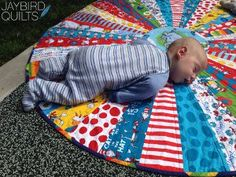 @Julie Herman has a creative way to use your scrappy quilt leftovers. The whole family will love this super easy circular quilt pattern. You can use it as a small baby quilt pattern, a table topper, and much more.