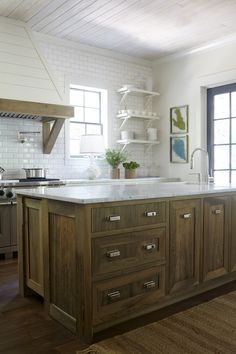 I like this look as a compromise between wood & white. I don't like the hood but I like the subway tile and marble tops to the natural wood. I would like it even better with concrete floors.