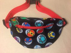 This is a fanny pack out side made of 100% cotton specialty fabric in a Pokemon Balls print and inside made of red denim fabric. It has a front zipper opening, and red webbing tie belt with a parachute clip for closure. The tie adjusts to fit from a toddlers to teenagers. Measure are 8 X 4 X 3  Waist measure adjustable from 24 inches to 33 inches.  For adults measures are 10x5x3 And waist measure adjustable for your size.  This fanny pack is great for any occasion, sports games, school or…