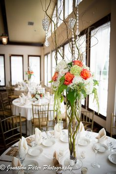 Tall wedding centerpieces with hydrangeas, roses, manzanita branches, and hanging crystals