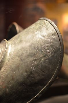 Greaves, Detail, Pompeii, Bronze, 1st Cent C.E.  Shin Guards, or greaves, were worn by gladiators for protection and to ward off blows during combat. The relief carvings on these shin guards feature Jupiter and Neptune. These greaves still have the rings at the back that would have held leather laces.