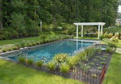 A rectangular pool by Carlton Pools, Inc. forms the perfect natural backyard oasis.