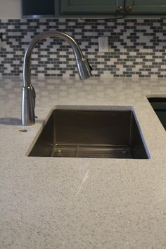 Love this kitchen remodel! Cambia Whitney Quartz stone countertops with a glass mosaic backsplash. Designed and installed by Florida Bath & Surfaces.