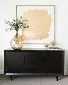 Chic bedroom features a gold abstract art placed over a black credenza adorned w. - Chic bedroom features a gold abstract art placed over a black credenza adorned with brass pulls top - Credenza Decor, Credenza Buffet, White Credenza, Sideboard Ideas, Modern Credenza, Black Sideboard, Home Design, Interior Design, Luxury Interior