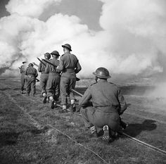 Royal Engineers move up through a smokescreen during training for the crossing of the River Garigliano in Italy, 18 January 1944.