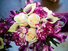 Bridesmaid bouquet: cream vendela roses, Picasso calla lilies, bicolor magenta carnations, purple alstroemerias, and self-stick gems. Fall wedding flowers. Credit: Megan Élan Photography.