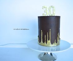 Upside down ganache drip painted gold on a chocolate ganache cake for a 30th!
