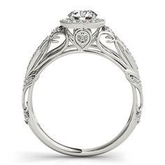 This is a beautiful handmade vintage engagement ring, Featuring a superb round brilliant I1 cut diamond encircled with a diamond halo accent. The