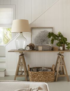 Foyer Decor - Coastal - Cottage - Foyer. Cottage foyer is filled with a seagrass basket filled with magazines tucked under wood sawhorse table with smoke gray glass lamp, framed sea fan.. #Cottage #Foyer Jenny Wolf Interiors.