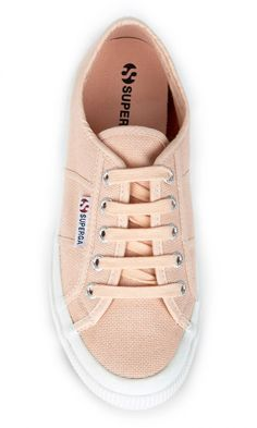 Iconic, pink/peach canvas sneakers by Superga. Italian-made with tonal ties, logo-embossed grommets and a wide rubber sidewall.