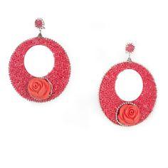 Pendiente flamenco en forma de aro en tono coral con engarces y detalles plateados. El pendiente está rematado con un rosa en el mismo tono coral.