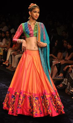 Orange lehenga with pink border and a colourful blouse with a blue dupatta.