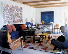 In the living room of his East Hampton, New York, home, designer Robert Stilin centered a French Art Deco rug from F. J. Hakimian atop an earthy sisal, adding graphic energy to the room's navy, gold, and brown color scheme.