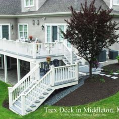 White stained cedar rails surround this grey Trex deck. Stairs and landings cascade down the slope and provide access to the side and back yards.