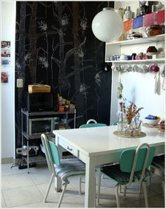 chalk wall with tree artwork, cups and saucer shelving, clear glass center table arrangement, retro chairs