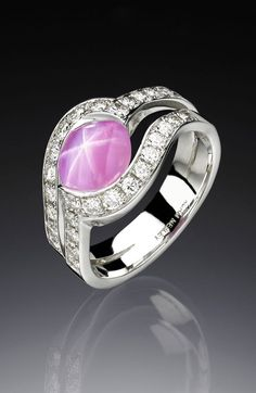 A modern ring design by Adam Neeley.  Rose Star Sapphire Ring is simply elegant, capturing the magic of love�s embrace. This unique ring design features dazzling pink star sapphire encircled by diamonds set in white gold.