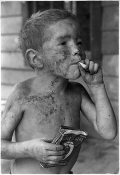 Boy covered by dirt smoking cigarette with one hand, holding can of tobacco in other. Kentucky, 1964. William Gedney