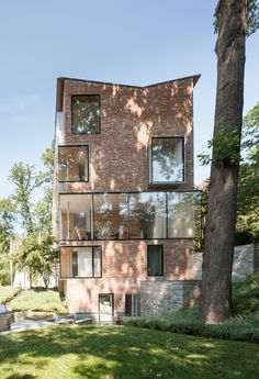 This 1920s four-story brick home in the Rock Creek neighborhood of Washington, D.C., fits into the neighborhood with a row of conservative homes, but the back presents a more unique facet—a line of windows, and a series of glass boxes jutting out from the main house. Inside is equally unique with unconventional forms in wall panels, deep window frames, and built-in shelving, all made from plywood. #dwell #modernarchitecture #modernbutteryflyroofs #butterflyroofs