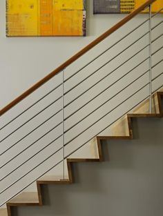 wood handrail with metal railing, wood stairs: Remodelista