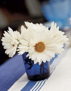 What a nice Idea for Creative Floral Arrangements - White Daisies in a Blue Vase. A simple cluster of  in a cobalt blue votive holder freshen up any table setting. Let this small arrangement stand alone as your main centerpiece, or line several down the center of a longer table.  #Whitedaisies #floralsetting #floralarrangement #daisies #flowers #tableflowers